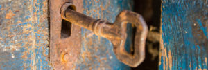 Old rusty metal key and keyhole on a blue cracked wooden door
